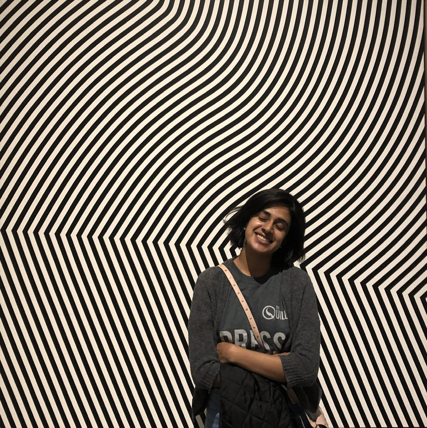Young woman standing in front of abstract art piece.