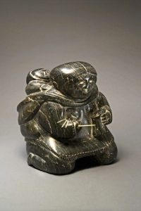 Pinnie (Benjamin) Naktialuk. <em>Mother Sewing Kamik (Skin Boot)</em>, 1954. Stone, ivory, black inlay, 33 x 28.1 x 28.1 cm. Collection of the Winnipeg Art Gallery. Gift of the Women's Committee, G-57-117. Photograph: Ernest Mayer